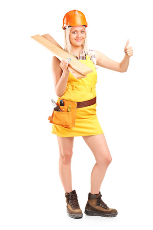 Female carpenter holding a couple of planks and giving thumb up isolated on white background   photo