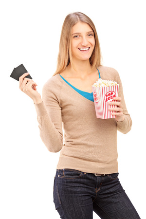 Girl holding two movie tickets and box of popcorn isolated on white background photo