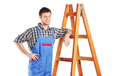 Male worker in jumpsuit standing next to a ladder isolated on white background photo