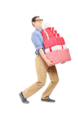 Man carrying a heavy load of presents isolated on white background photo