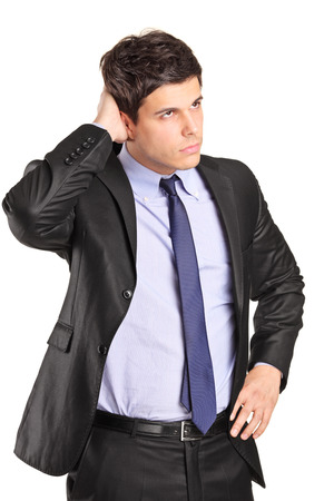 Confused young businessman looking in the distance isolated on white background photo