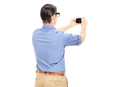 Man taking a picture with cell phone isolated on white background photo