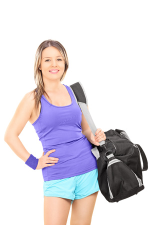 Female athlete carrying a sports bag isolated on white background