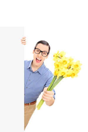 Man holding flowers behind a blank panel isolated on white background photo