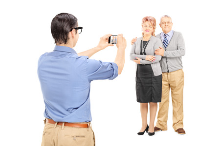 Young man taking picture of a mature couple isolated on white background photo