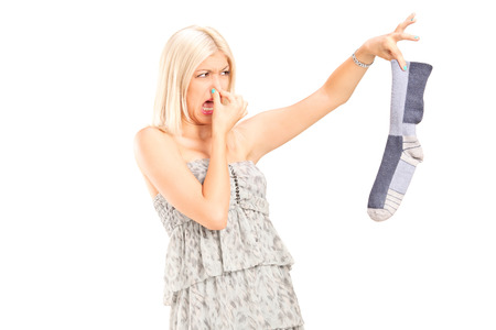smelly: Woman holding a stinky sock isolated on white background Stock Photo