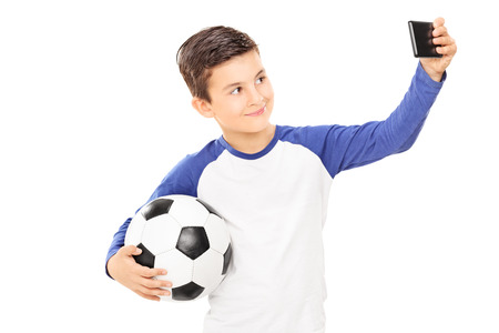 kids football: Boy holding football and taking a selfie isolated on white background Stock Photo