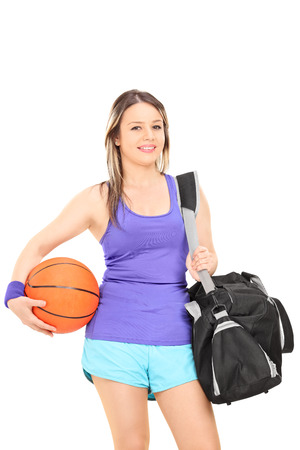 Woman holding basketball and a sports bag isolated on white background photo