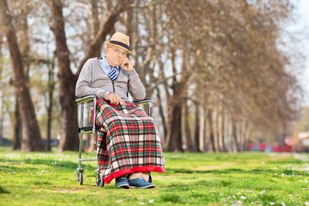 grumpy old man: Grumpy old man sitting in a wheelchair outdoors
