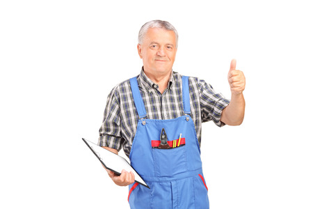 studio happy overall: Male mechanic holding clipboard and giving thumb up isolated on white background