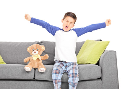 Little boy yawning seated on couch isolated on white background photo