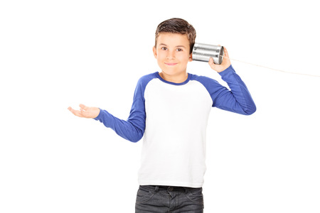 Little boy listening through a tin can phone isolated on white background photo