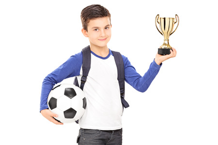 Little schoolboy holding football and a trophy isolated on white background photo
