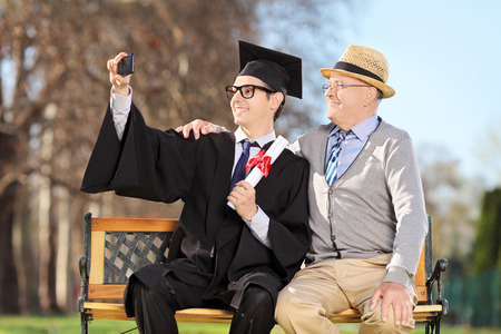Male graduate and his father taking selfie outdoors photo