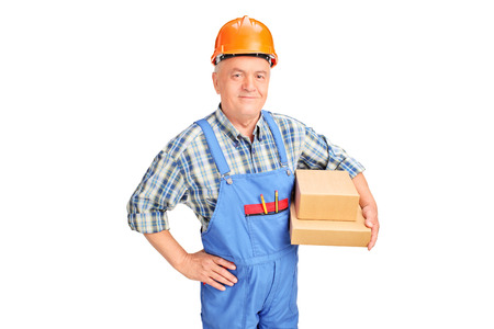 studio happy overall: Mature construction worker holding boxes isolated on white background