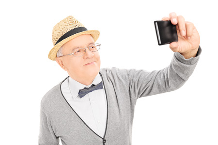 Senior gentleman taking a selfie with cell phone isolated on white background Stock Photo