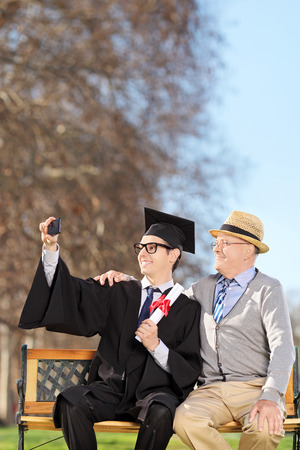 Student and his proud father taking selfie outdoors photo