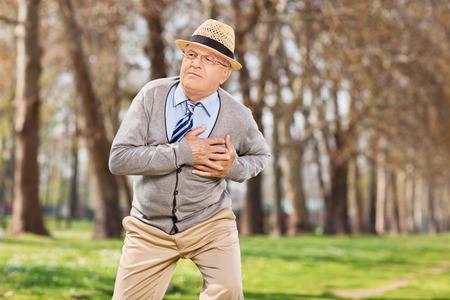 cardiac arrest: Senior having a cardiac arrest outdoors, in the park