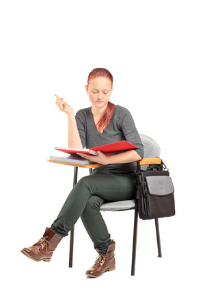 seated: Female student seated on school desk and reading a book isolated on white background