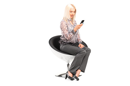 Stylish woman looking at a cell phone isolated photo