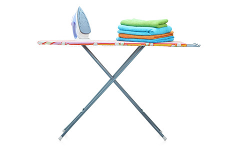 Studio shot of an ironing board with clothes on it isolated on white background