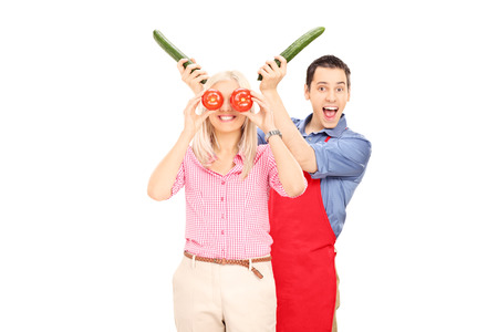 Young couple having fun with vegetables isolated on white background  photo