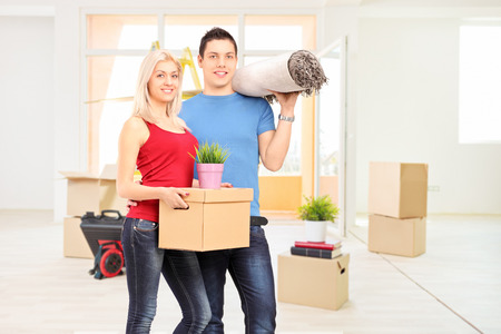 Young couple moving into a new apartment full of moving boxes photo