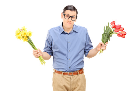 indecisive: Indecisive man holding red and yellow tulips isolated on white background
