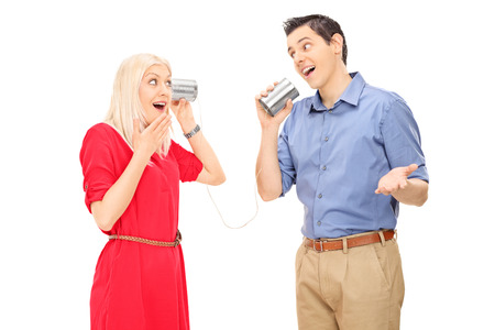 Man and woman talking through a tin can phone isolated on white background photo