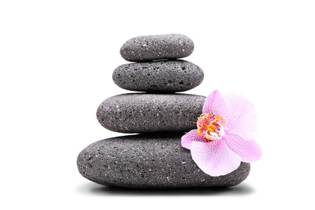 Stack of balanced stones and a pink flower isolated on white background photo