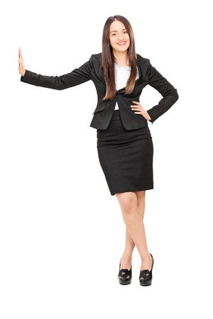 Businesswoman leaning against a wall isolated on white  photo
