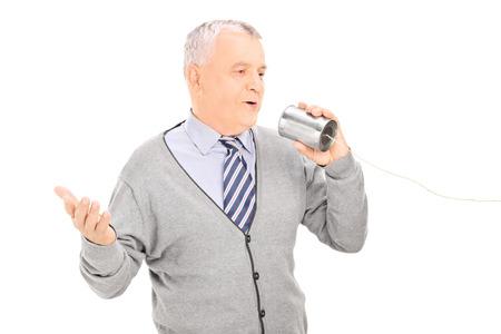 tin can telephone: Senior man talking through a tin can phone isolated on white