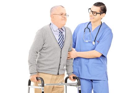 ancianos caminando: Enfermero ayudando a un hombre mayor con el caminante aislado