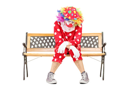 sad man alone: Sad clown sitting on a wooden bench isolated on white background