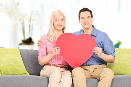 Young couple holding a big red heart indoors photo