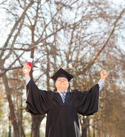 Mature graduate holding diploma and gesturing happiness outdoors shot with tilt and shift lens photo
