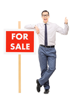 posing  agree: Excited man leaning on a for sale poster and giving thumb up isolated on white background