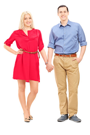 young couple smiling: Full length portrait of a young couple holding hands isolated on white background Stock Photo