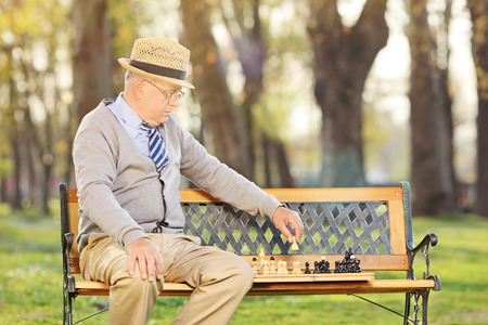 Senior adult playing chess alone outdoors  seated on wooden bench photo