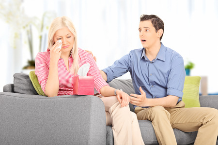 consoling: Young husband comforting his sad wife seated on sofa at home Stock Photo