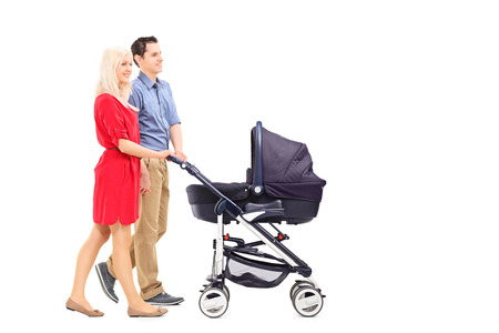 Young parents pushing a baby stroller isolated on white background photo