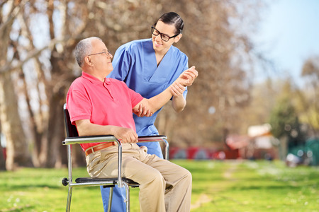Male nurse checking the pulse of a senior in park photo