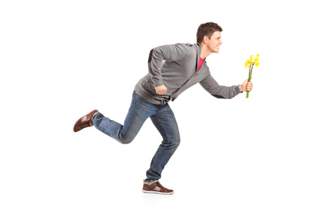 running late: Man running with yellow tulips in hand isolated