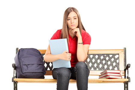 Female student contemplating seated on a bench isolated  photo