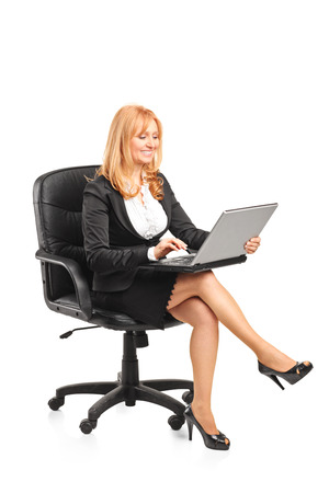 Mature businesswoman working on laptop seated on chair isolated on white background photo