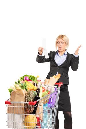 caras emociones: Mujer Formal mirando la factura comercial con incredulidad aisladas sobre fondo blanco
