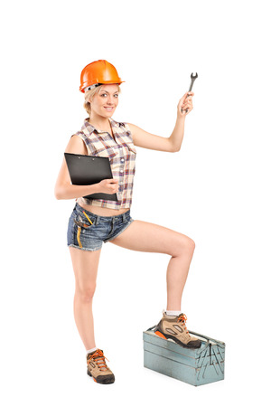 Full length portrait of a female mechanic holding a wrench and stepping onto a toolbox isolated on white background photo