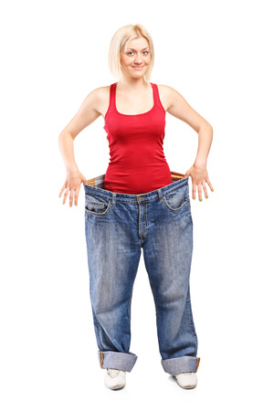 oversized: Woman standing in a pair of oversized jeans isolated on white background