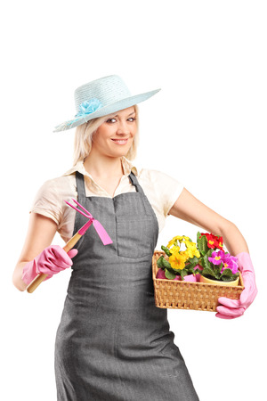 mattock: Female gardener holding a mattock and a basket with flowers isolated on white background Stock Photo