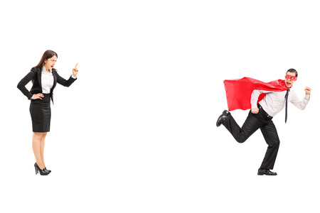 Superhero running away from an angry businesswoman isolated on white background photo